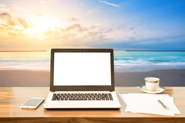 Mockup image of laptop with blank white screen,smart phone and document on wooden table at landscape early morning sunrise over the sea the horizon background.