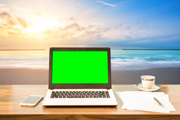 Mockup image of laptop with blank green screen ,smart phone and document on wooden table at landscape early morning sunrise over the sea the horizon background.