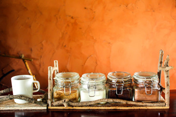 Coffee beans, coffee powder, creamer, cocoa powder and processed tea leaves in a mason jar orange brick wall