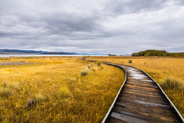 Wooden boardwalk in the Mono Lake Tufa State Natural Reserve on a cloudy autumn day, California