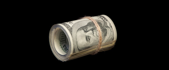 A roll of one hundred dollar bills tied with a rope. On a black background.