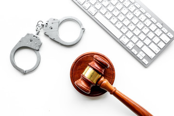Arrest of a hacker for cyber fraud concept. Handcuff near keyboard and judge gavel on white background top view