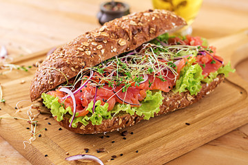 Keuken foto achterwand Snack Salmon sandwich - smorrebrod with cheese cream and microgreen on wooden table.