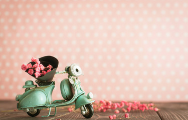 Vintage toy blue mototrcycle with bunch of pink flowers on wooden table