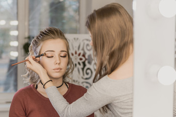 professional makeup artist makes makeup beautiful girl in a beauty salon