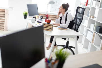 A young girl is sitting at the computer desk in the office.