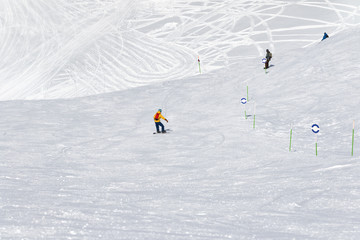Skiers and snowboarders downhill on snowy ski trace