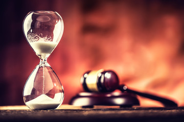 Modern hourglass in running time and justice hammer on wooden table