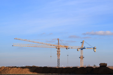 An image of a tower crane against the background of a house under construction.