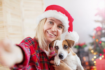 Happy woman with dog in christmas decoration