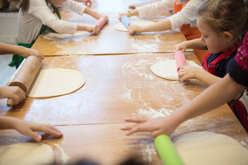Hands of children rolling pizza dough with rolling pin on the kitchen table. Cooking pizza.