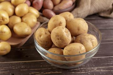 Fresh potatoes on the wood background