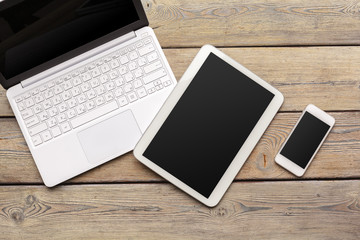 Open laptop with digital tablet and white smartphone close up top view