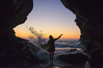 silhouette of a girl in the sunset light on the background of the sea