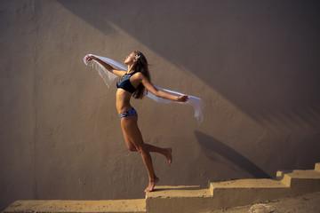 girl in a bathing suit dancing in a beautiful light