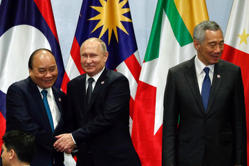 Vietnam's Prime Minister Nguyen Xuan Phuc shakes hands with Russian President Vladimir Putin during a group photo with other ASEAN leaders at the ASEAN-Russia Summit in Singapore