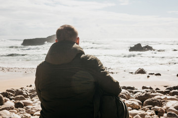 A man with a backpack or a tourist or a traveler in solitude admires a beautiful view of the Atlantic Ocean in Portugal. Search for soul or unity with nature.