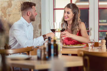 Young smiling couple enjoying red wine on their date