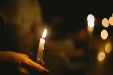 soft focus of people lighting candle vigil in darkness seeking hope, worship, prayer