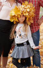 Girl posing with yellow leaves on her head. Happy family is in autumn city park. Children and parents. They posing, smiling, playing and having fun. Bright yellow trees.