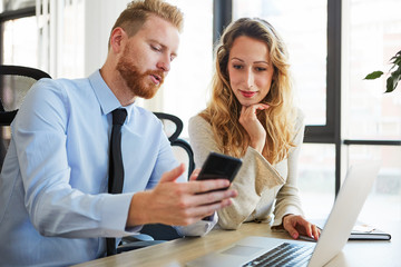 Two colleagues in office, he is showing her something on mobile phone