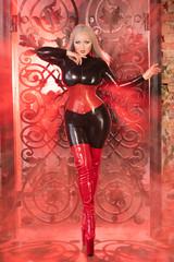 beautuful luxury blonde girl posing in high fetish fashion latex costume near huge gates with smoke alone