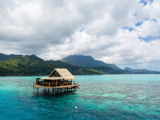 Lonely overwater bungalow of black pearl farmers. Blue azure turquoise lagoon with corals. Emerald Raiatea island, French Polynesia, Oceania.