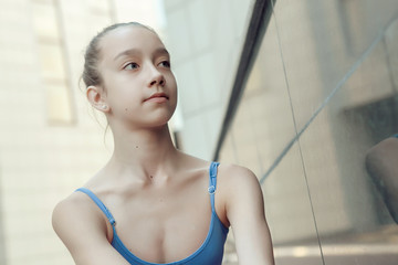 Portrait of ballet dancer dancing outdoor. Young ballerina in blue sportwear. Portrait of young lovely pretty beautiful girl in the park.
