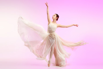 Young graceful female ballet dancer or classic ballerina dancing at pink studio. Caucasian model on pointe shoes