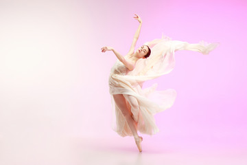 Young graceful female ballet dancer or classic ballerina dancing at pink studio. Caucasian model on...