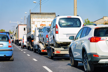 Car carrying trailer with new vehicles on road of Slovenia