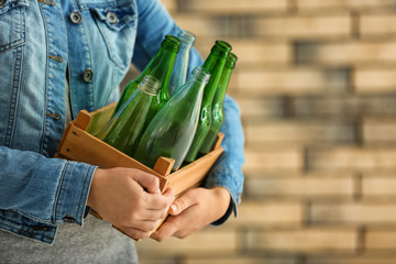 Woman holding wooden box with empty glass bottles near brick wall