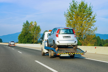 Tow truck transporter carrying car in Road in Slovenia