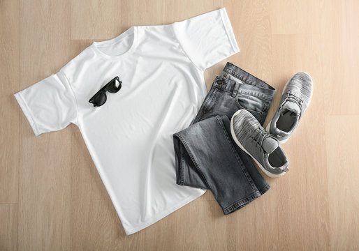 Composition with white t-shirt, jeans and shoes on wooden background