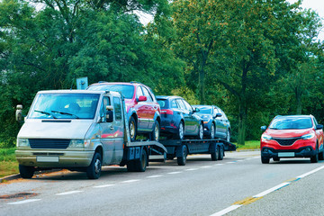 Car carrying trailer with new vehicles on road Slovenia