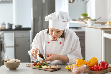 Young female chef pouring sauce onto tasty dish in kitchen