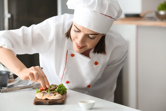 Young female chef preparing tasty dish in kitchen