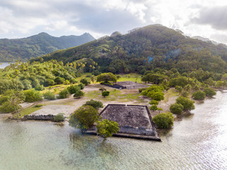 Ancient Marae Taputapuatea temple complex on the lagoon shore with mountains on background. Raiatea island. French Polynesia, Oceania.