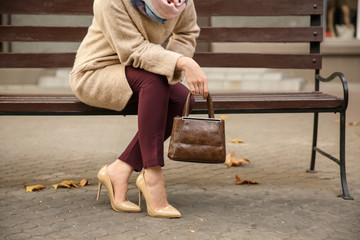 Beautiful fashionable woman sitting on bench outdoors