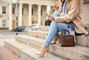 Beautiful fashionable woman with mobile phone sitting on steps outdoors Wall mural