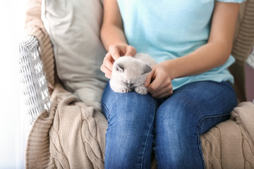 Young woman with cute little kitten at home