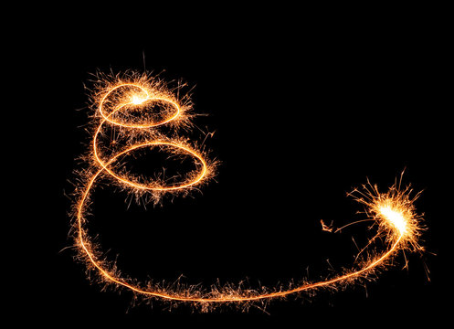 Shining spiral made of sparklers on dark background