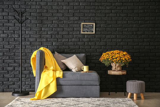 Comfortable armchair with beautiful chrysanthemum flowers near dark brick wall
