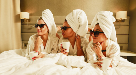 Friends in towels and bathrobes are sitting on the bed.