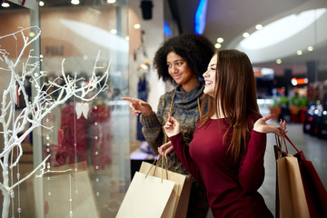 Young multiethnic diverse race women with paper shopping bags near decorated shopwindow. Girl pointing by finger at shopfront, clothes and products in mall on christmas new year sale.