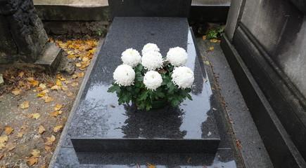 Pots de chrysanthèmes blancs sur une tombe en pierre noire mouillée par la pluie