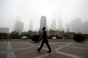Man wearing a mask walks in the central business district on a polluted day after a yellow alert was issued for smog, in Beijing