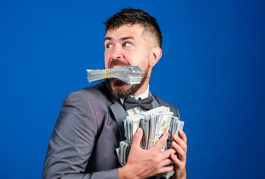 Steal money. Thief with piles dollars money. Earnings surprise concept. Man bearded businessman hold pile money blue background. Businessman surprised feels like thief with lot of cash in hands