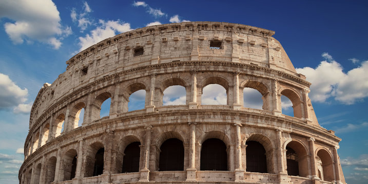 Detail of the arches of the Colosseum. Marble ruins over a blue sky, Rome, Italy