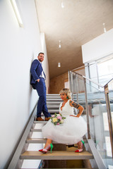 Elegant couple of newlyweds pose on a staircase